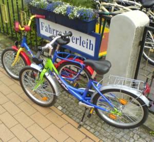 Zwei bunte Kinderfahrräder auf dem Gehweg stehend vor dem Standort Bansin vom Usedom Fahrradverleih